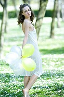Young woman walking in meadow, holding balloons, looking over shoulder at camera