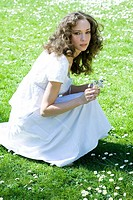 Young woman crouching in meadow, picking flowers, looking up at camera