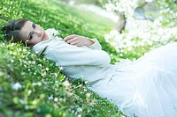 Teenage girl lying on the ground, holding flowers, looking at camera