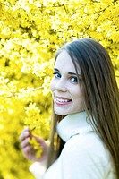 Teenage girl next to flowering tree, smiling over shoulder at camera