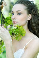 Young woman holding flowering tree branch, looking at camera, close-up