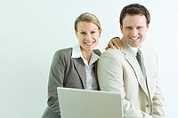 Male and female business associates using laptop computer together, both smiling at camera