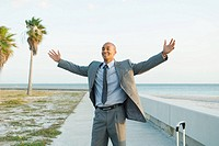 Businessman standing near beach with arms raised, smiling