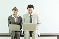 Male and female business associates sitting side by side, both using laptop computers