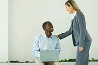 Teenage boy sitting, using laptop computer, smiling up at businesswoman standing beside him
