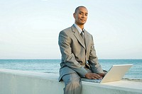 Businessman sitting on low wall by the sea, using laptop computer, smiling at camera