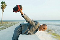 Businessman leaning over low wall at the beach, holding up football, smiling at camera