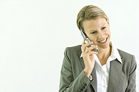 Businesswoman using cell phone, smiling, looking down