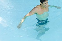 Man standing in swimming pool, high angle view