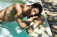 Man leaning against side of swimming pool, resting head on arms, eyes closed