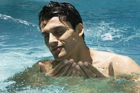 Man splashing in swimming pool, eyes closed, close-up