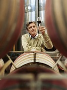 Mature man holding up glass of wine in wine cellar