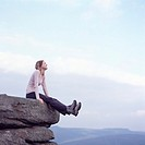 Young woman sitting on rock edge with legs stretched out