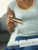 Woman in front of computer keyboard with credit card