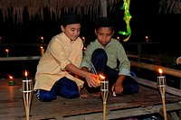 Two boys lighting lamps for Hari Raya, Malaysia