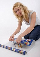 young woman wrapping presents with gift wrap paper