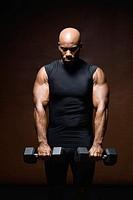 Man lifting weights, studio shot