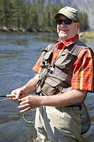 Portrait of senior man smiling while flyfishing