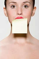 Woman with adhesive note on her mouth