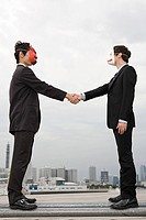 Businessmen wearing masks shaking hands