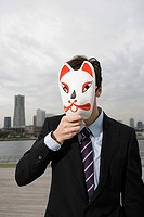Portrait of a businessman waering a cat mask