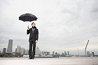 A businessman holding an umbrella (thumbnail)