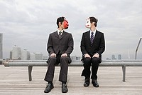 Businessmen wearing masks sat on a bench