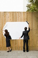 Businesspeople attaching paper to a fence
