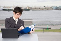A businessman writing on a clipboard