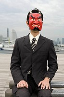 Portrait of a businessman wearing a devil mask