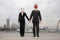 Businesspeople wearing masks holding hands
