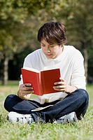 Young man reading in park