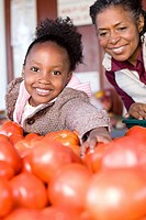 A girl with her grandmother choosing tomatoes
