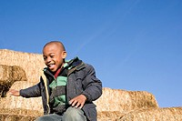 Boy playing on bales of hay