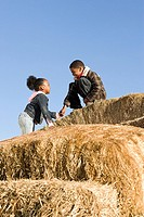 Brother helping his sister climb bales of hay