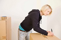 Woman writing on cardboard box