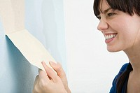 Woman removing wallpaper