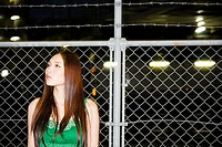 Young woman standing near a wire fence