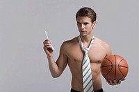 Man wearing neck tie and holding basketball
