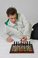 Man lying down on floor and playing chess