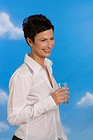 Young woman holding glass of water, smiling, portrait