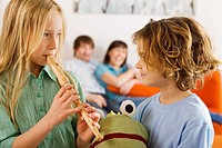 Boy 6_7 and girl 8_9, playing recorder
