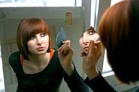 Woman looking into mirror, portrait