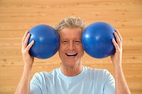 Man holding two gymnastic balls, smiling, portrait