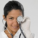 Portrait of smiling young female doctor holding stethoscope in front of one eye