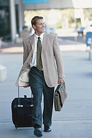 Businessman walking in airport with luggage, looking away