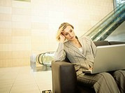 Businesswoman sitting in armchair with laptop