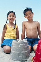 Boy 6_9 and girl 4_7 sitting besides sandcastle, smiling, portrait