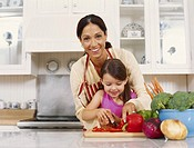 Mother and daughter 3_5 cutting vegetables in kitchen