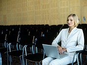 Businesswoman sitting in conference room with laptop